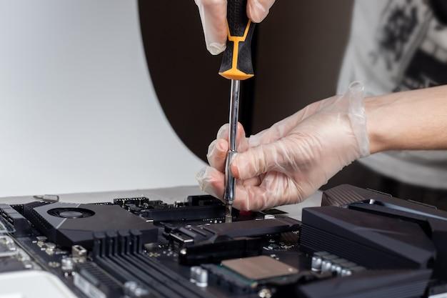 기술자가 컴퓨터 마더 보드에 새로운 고속 고용량 Ssd 드라이브를 설치하고 있습니다. 프리미엄 사진