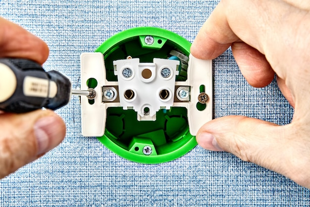 Техник заменяет сломанную электрическую розетку.