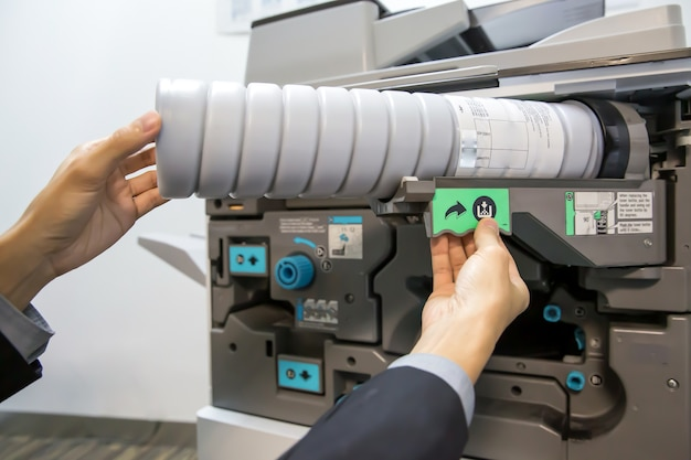 The technician is replacing the copier ink