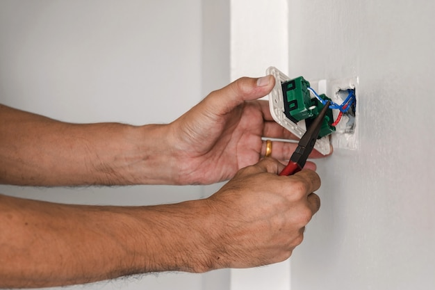 The technician is using a pliers to install the power plug on the wall