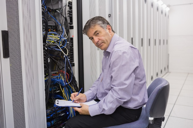 Technician looking up from making notes on server