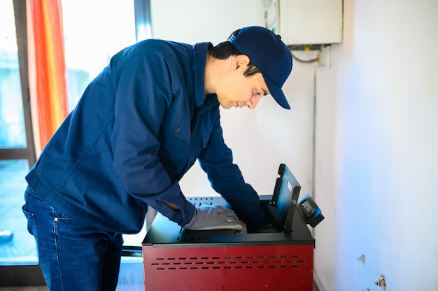 ペレット収納ヒーターを維持する技術者