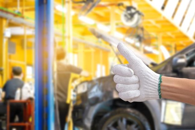Техник человек дает большой палец вверх с автосервисным центром размытым фоном