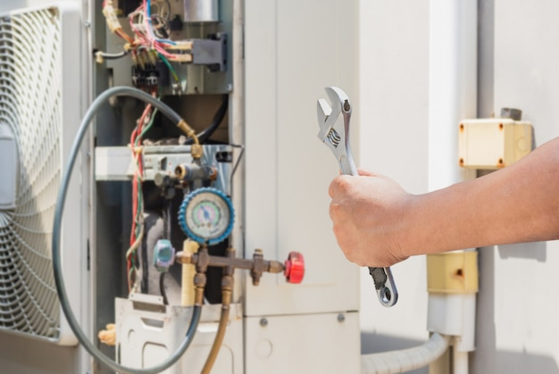 Руки человека техника держа ключ над запачканной современной концепцией кондиционирования воздуха, обслуживания и ремонта