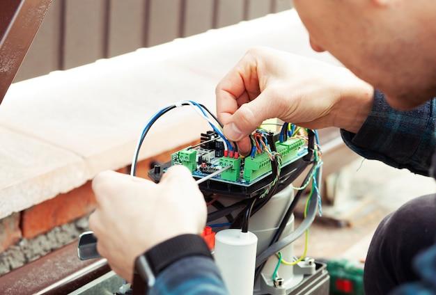 Техник, устанавливающий и проверяющий функцию автоматических ворот