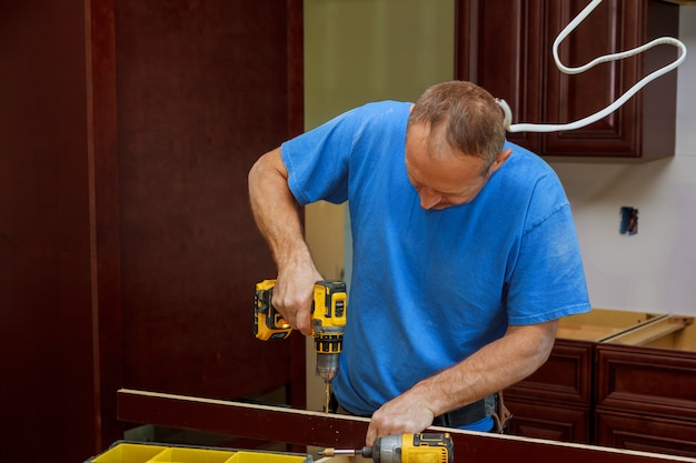 Technician man installing kitchen cabinets