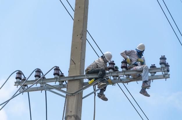 기술자들은 전주에 있는 끊어진 전력선을 수리하거나 수리하는 매우 위험한 작업입니다.