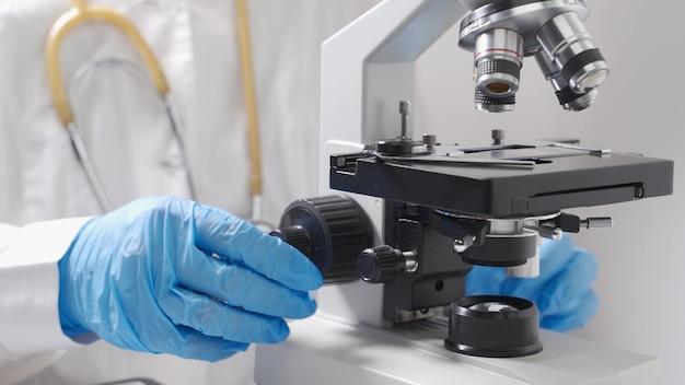 Техник здоровья с кровью в клинической лаборатории аналитических, медицинских, фармацевтических. подготовка образца крови для анализа под микроскопом. руки заделывают. больничный анализ крови.