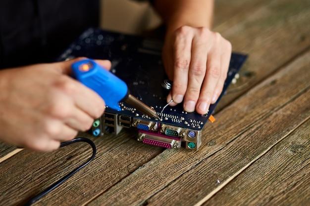 Техник или инженер сосредоточен на ремонте печатной платы с паяльником.