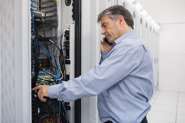 Technician phoning while repairing a server
