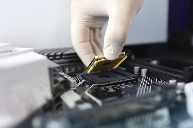 Technician plug in cpu microprocessor to motherboard socket. workshop background.