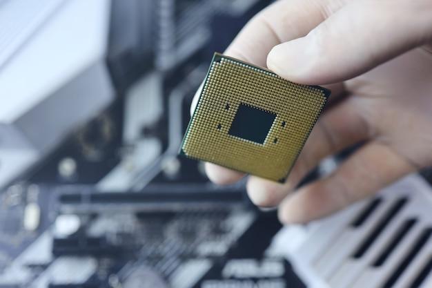 기술자가 cpu 마이크로프로세서를 마더보드 소켓에 연결합니다. 워크샵 배경입니다.