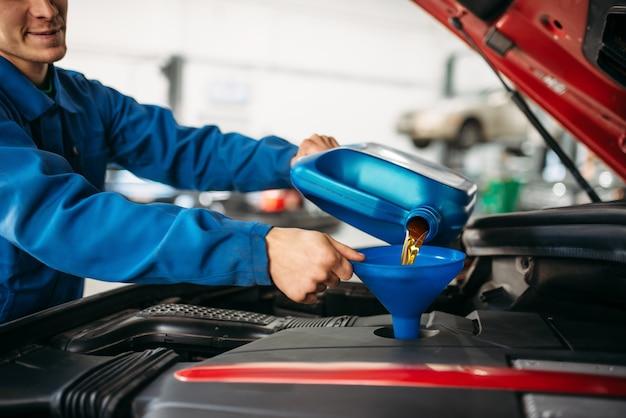 Техник наливает новое масло в двигатель автомобиля