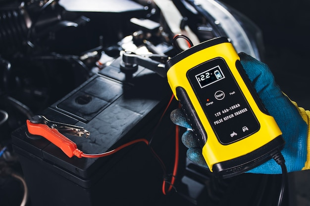 Technician recharge car battery with automatic battery charger in repair garage