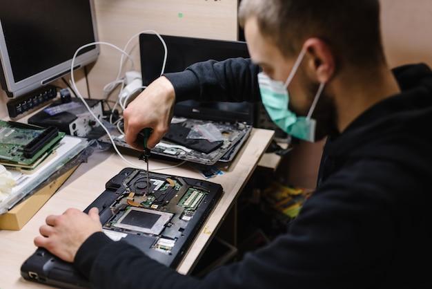 ラボでノートパソコンを修理する技術者。修理コンピューター、電子、アップグレード、技術の概念。コロナウイルス。男は働いて、ワークショップで防護マスクを着ています。