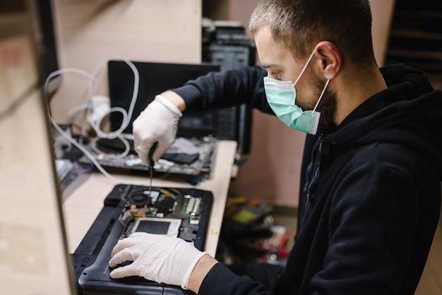 ラボでノートパソコンを修理する技術者。男は働いて、ワークショップで防護マスクを着ています。