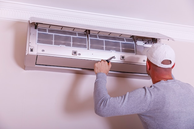 Technician repairing air conditioner on the wall. dirty filter of air conditioner in female hands. cleaning and washing maintenance.
