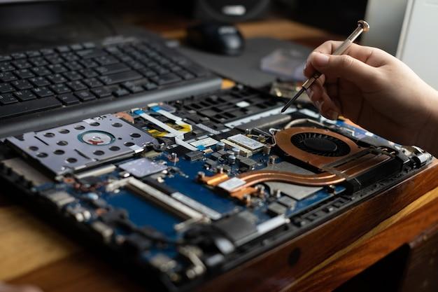 Техник, ремонтирующий сломанный портативный компьютер с отверткой