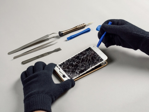 Technician repairing broken smartphone on desk