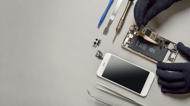 Техник ремонтирует сломанный смартфон на столе