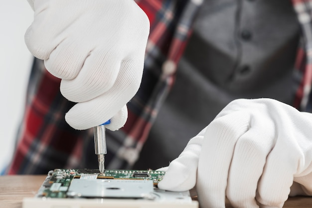Technician repairing computer motherboard with screwdriver