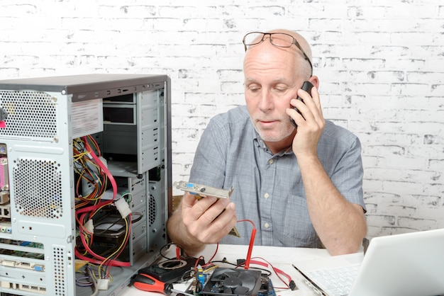A technician repairing a computer and phone