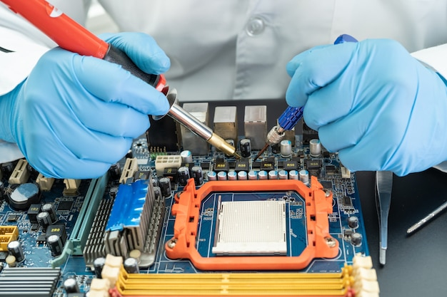 Technician repairing hard disk by soldering iron.