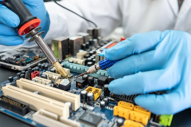 Technician repairing inside of hard disk by soldering iron integrated circuit