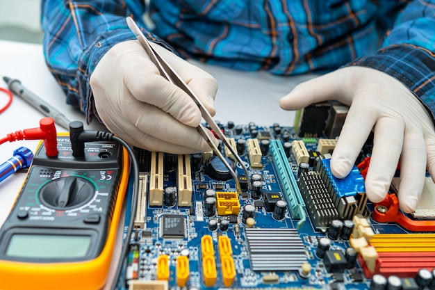 Technician repairing inside of hard disk by soldering iron.