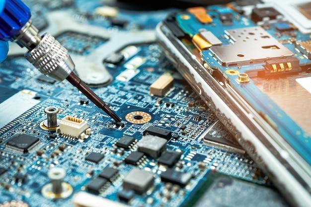 Техник ремонтирует жесткий диск с помощью паяльника. интегральная схема. понятие данных, оборудования, техника и технологии.