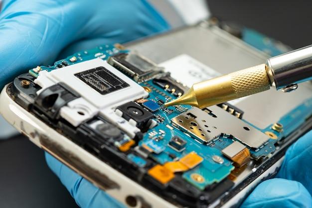 기술자는 인두를 납땜하여 하드 디스크 내부를 수리합니다. 집적 회로. 데이터, 하드웨어, 기술자 및 기술의 개념입니다.