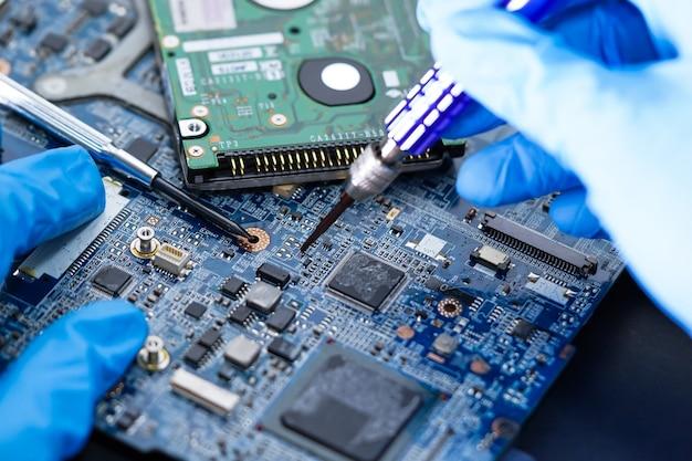 Техник ремонта внутри жесткого диска с помощью паяльника.