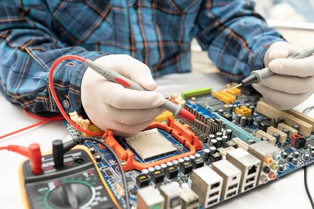 技術者は、はんだごてによってハードディスクの内部を修復します。