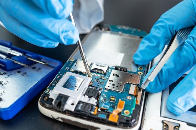 携帯電話の内部をはんだごてで修理する技術者。集積回路。データ、ハードウェア、テクノロジーの概念。