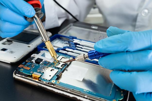 납땜 인두로 휴대 전화 내부 수리 기술자. 집적 회로. 데이터, 하드웨어, 기술의 개념.