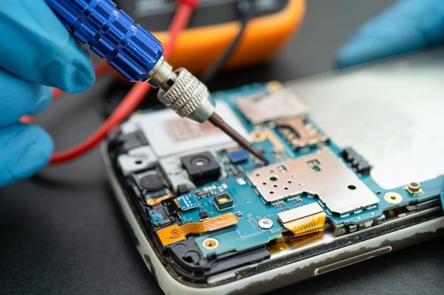 인두를 납땜하여 휴대폰 내부를 수리하는 기술자. 집적 회로. 데이터, 하드웨어, 기술의 개념입니다.