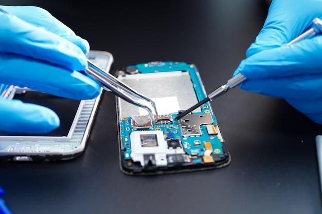 Техник, ремонтирующий внутри мобильного телефона.