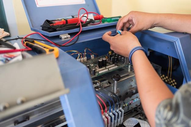 インクジェットプリンターのカラーディスペンサーのメインボードシステムを修理する技術者