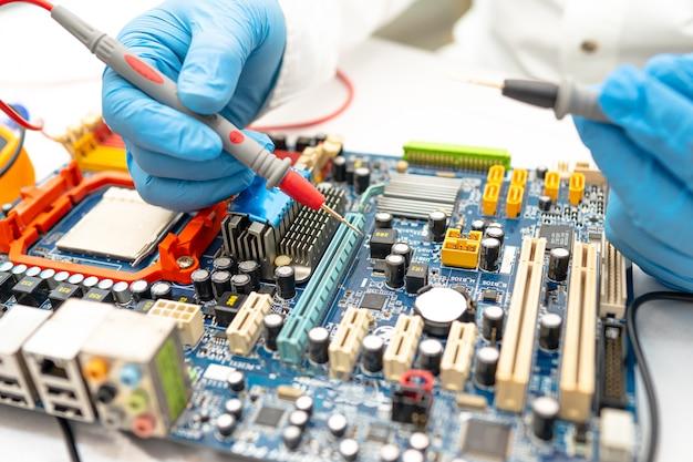Technician repairing micro circuit main board computer.