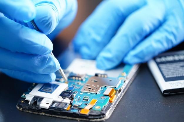 Technician repairing micro circuit main board of smartphone.