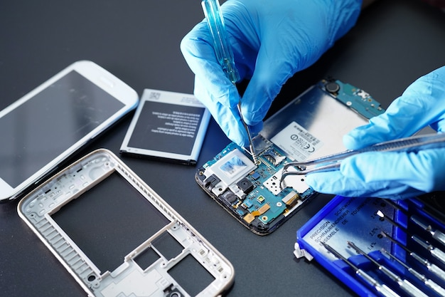 Technician repairing micro circuit main board of smartphone.