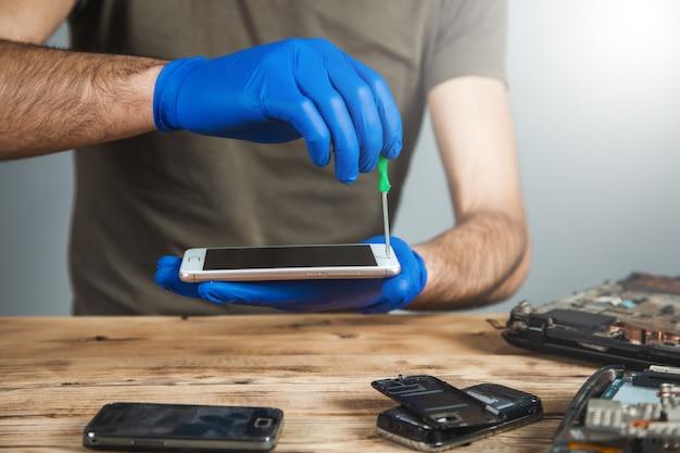 Техник, ремонтирующий мобильный телефон за столом