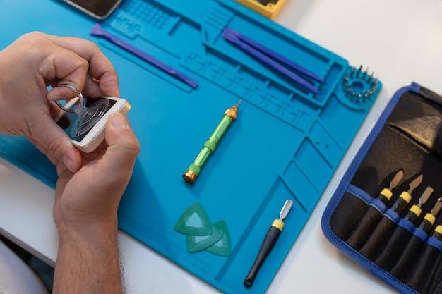 ツールで携帯電話を修理する技術者