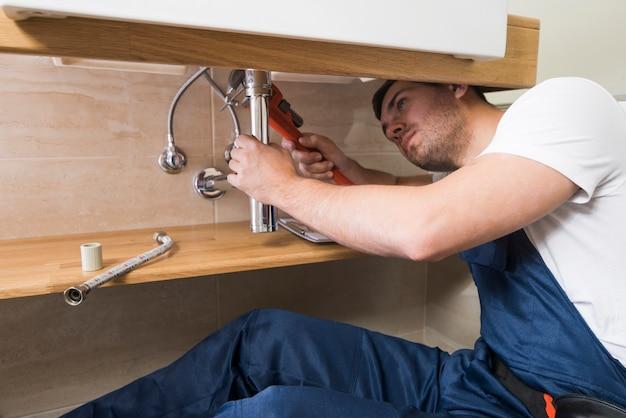 Техник, ремонтирующий раковину в ванной комнате