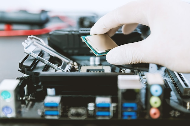 Technician replace cpu microchip in the cpu socket on the motherboard