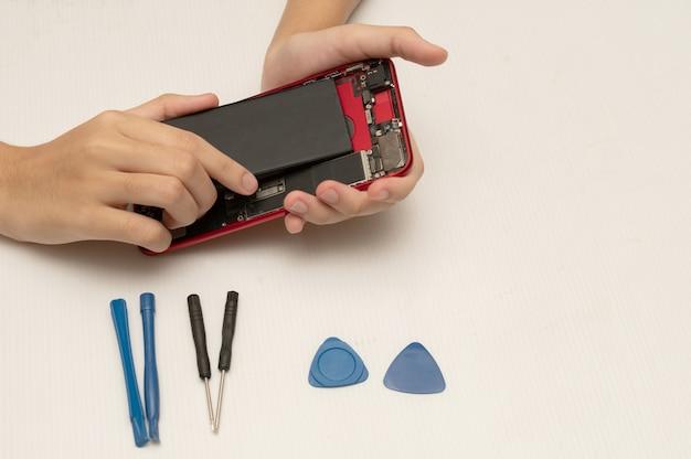 Техник заменяет аккумулятор мобильного телефона или смартфона.
