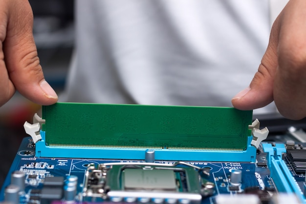 Technician's hands installing user memory on a computer main-board