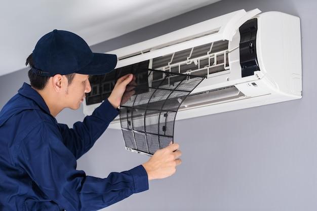 청소를 위해 에어컨의 공기 필터를 제거하는 기술자 서비스