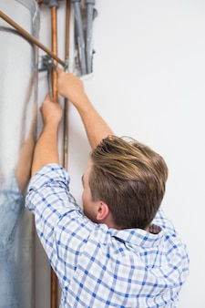 Technician servicing an hot water heater pipes