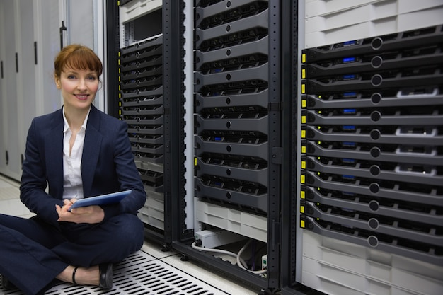 Technician sitting on floor beside server tower using tablet pc